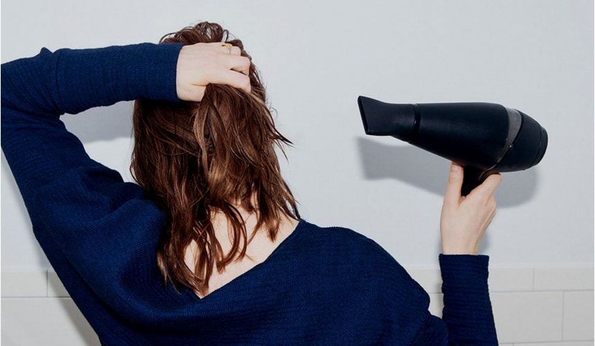 ドライヤーで髪を乾かしている女性